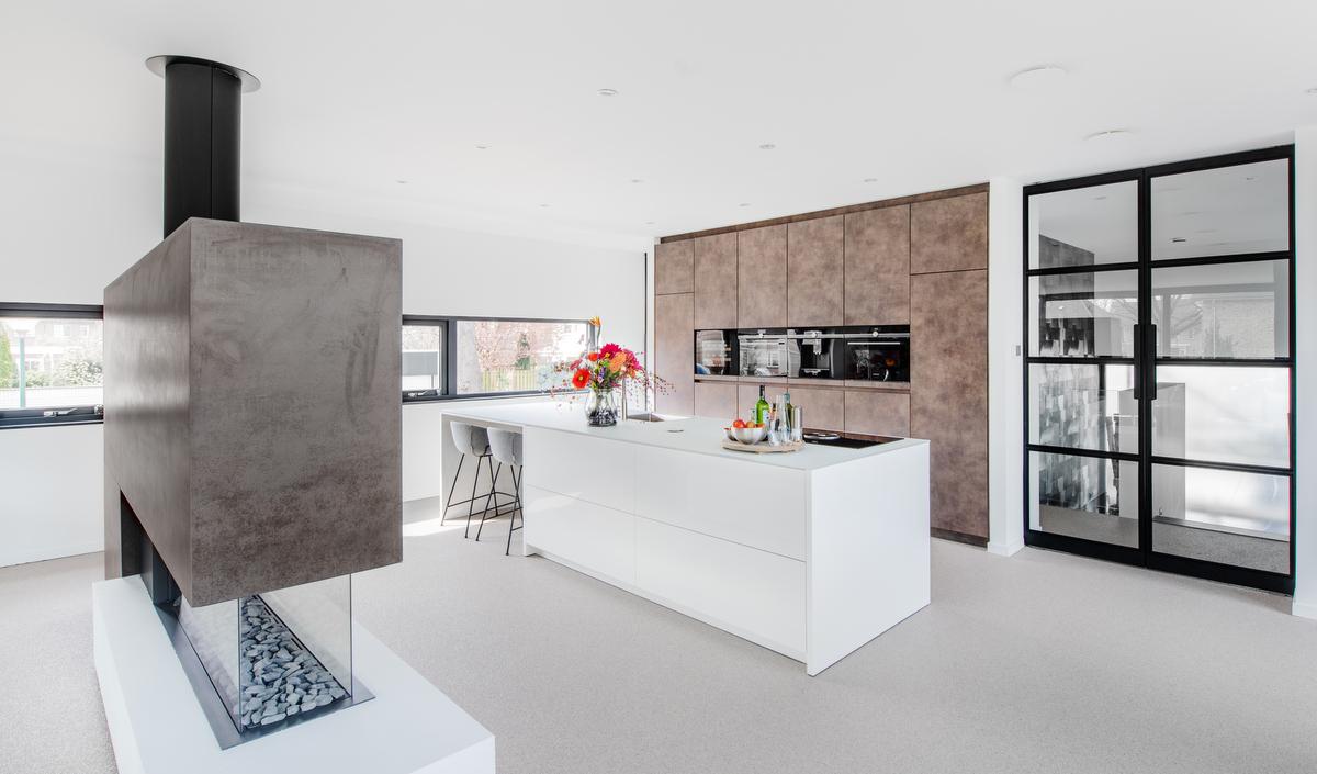 Warme strakke keuken met lederlook apparatenwand en glazen blad